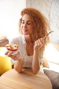 Glückliche rothaarige junge dame, die im café beim essen des nachtischs sitzt.