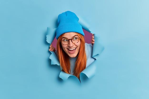 Glückliche rothaarige junge frau kichert positiv und schaut zur seite hat spaß fühlt sich unterhalten trägt optische brille blauer hut schaut durch zerrissenes papierloch