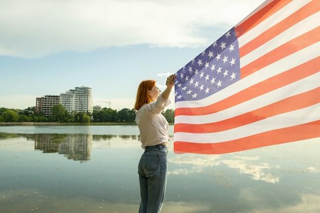 Glückliche rothaarige junge frau mit der nationalflagge der vereinigten staaten in der hand.