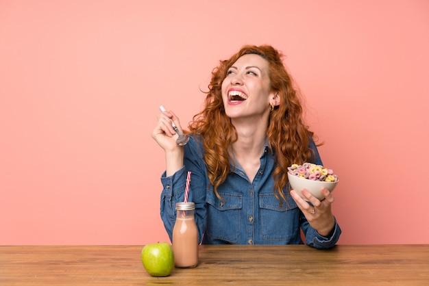 Glückliche rothaarigefrau, die frühstückt