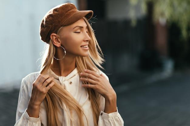 Glückliche ruhige junge gebräunte blonde frau in brauner mütze und weißem hemd lächelt aufrichtig und posiert draußen