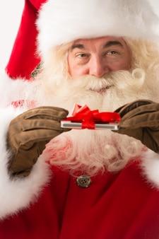 Glückliche santa claus, die geschenkgerät in seinen händen mit band hält