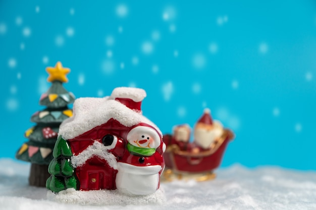 Glückliche santa claus mit geschenkkasten auf dem schneeschlitten, der geht, haus zu schneien.