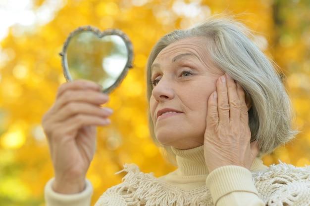Glückliche schöne ältere frau mit spiegel im herbstpark
