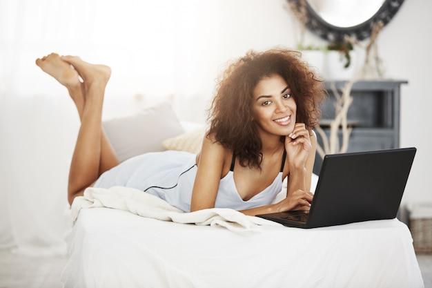 Glückliche schöne afrikanische frau in nachtwäsche liegend mit laptop auf bett zu hause lächelnd.