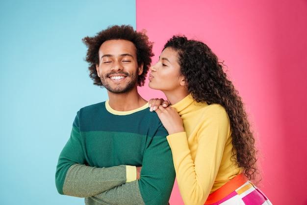 Glückliche schöne afrikanische junge frau, die ihren freund küsst