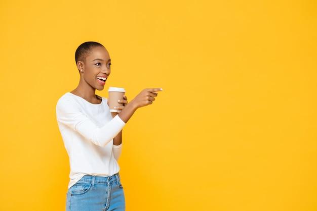 Glückliche schöne afroamerikanerfrau, die lächelnden kaffee trinkt und auf leeren raum beiseite zeigt, der auf gelber wand lokalisiert wird