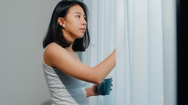 Glückliche schöne asiatin, die einen tasse kaffee oder einen tee nahe dem fenster im schlafzimmer lächelt und trinkt. offene vorhänge des jungen lateinischen mädchens und entspannen sich am morgen. lifestyle lady zu hause.