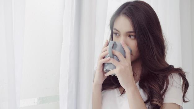 Glückliche schöne asiatin, die einen tasse kaffee oder einen tee nahe dem fenster im schlafzimmer lächelt und trinkt.