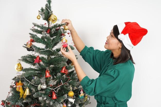 Glückliche schöne asiatische frau, die grünes kleid und weihnachtsmütze trägt weihnachtsfeier