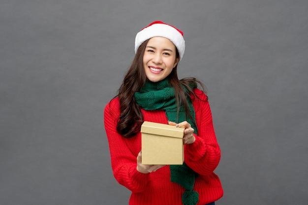 Glückliche schöne asiatische frau in der weihnachtskleidungsöffnungsgeschenkbox