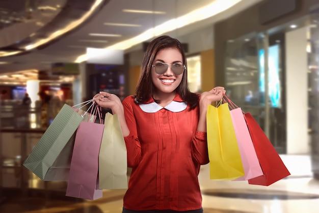 Glückliche schöne asiatische frau mit einkaufstüten