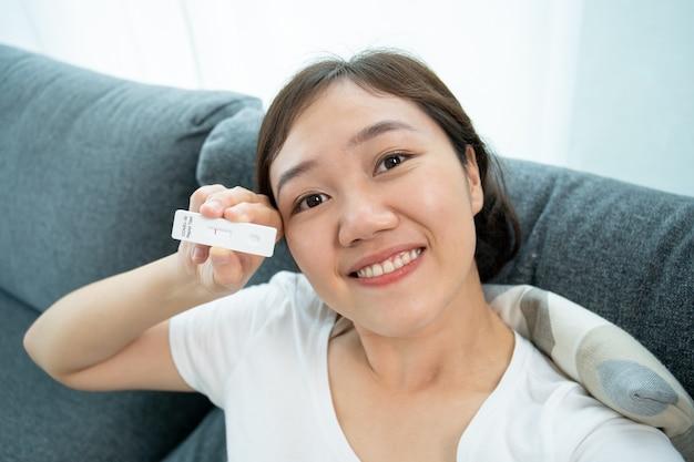 Glückliche schöne asiatische junge frau, die ein negatives ergebnis des covid-19- oder sars 2019-ncov-antigen-testergebnisses zur kamera zeigt, während sie einen videoanruf mit ihrer familie und ihrem arzt tätigt. covid-19-ag-test zu hause.