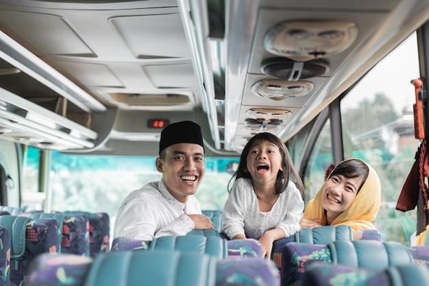 Glückliche schöne asiatische muslimische urlaubsreise, die einen bus zusammen mit familie während eid mubarak feier reitet