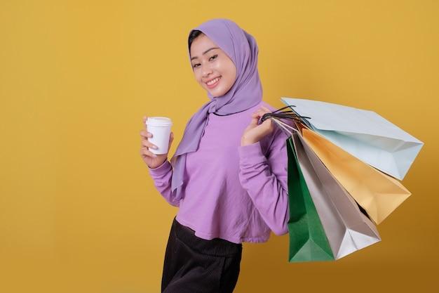 Glückliche schöne asiatische shopaholic frauen bringen ein glas getränk und halten einkaufstüten, lächeln und fröhlich