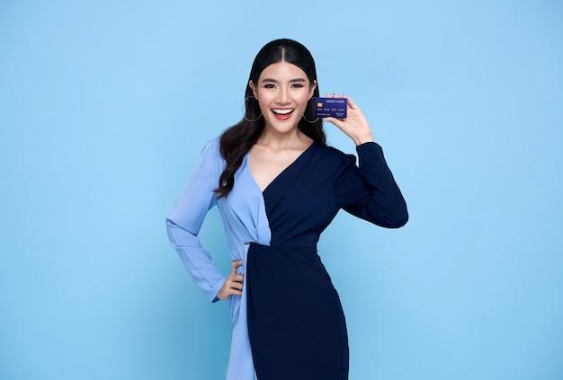 Glückliche schöne asiatische shopaholic frauen, die blaues kleid tragen, das kreditkarte in der hand auf blau zeigt.