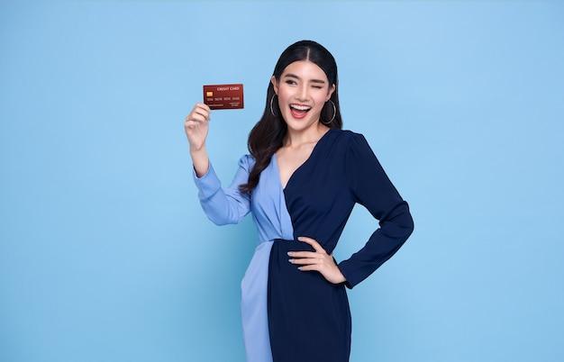 Glückliche schöne asiatische shopaholic frauen, die blaues kleid tragen, das kreditkarte in der hand lokalisiert auf blau zeigt.