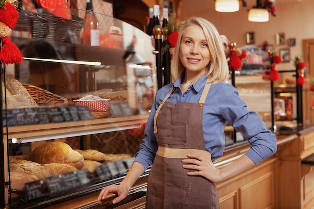 Glückliche schöne bäckerin posiert stolz in ihrem bäckereigeschäft, kopieren raum