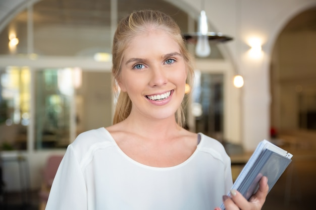 Glückliche schöne blonde frau, die weißes hemd trägt, im gemeinsamen arbeitsraum steht, notizblock mit papieren hält, posiert,