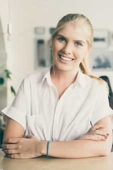 Glückliche schöne blonde frau, die weißes hemd trägt, im zusammenarbeitenden raum steht und sich auf schreibtisch stützt