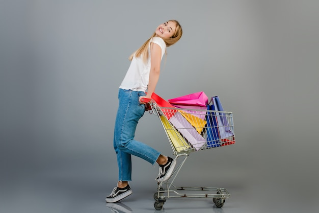 Glückliche schöne blonde frau hat handwagen mit den bunten einkaufenbeuteln, die über grau getrennt werden