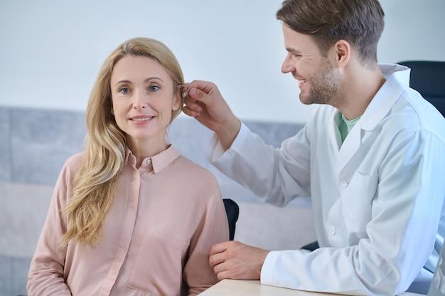 Glückliche schöne blonde kaukasische frau mittleren alters, die während der installation der gehörlosenhilfe in der arztpraxis sitzt