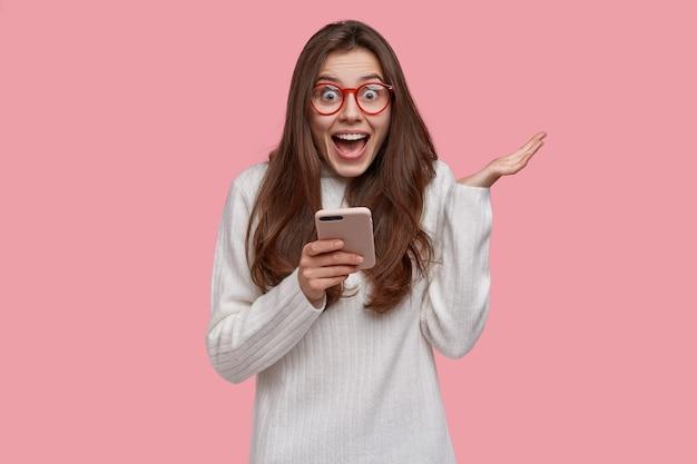 Glückliche schöne dame mit attraktivem blick, hebt hand, hat ausdruck überglücklich als empfangene nachricht mit geständnis in der liebe, texte im online-chat erhalten