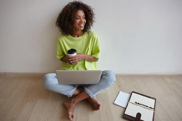 Glückliche schöne dunkelhäutige lockige frau, die über hauptinnenraum mit tasse kaffee in der hand und laptop auf beinen aufwirft und mit breitem lächeln beiseite schaut