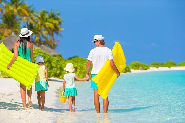 Glückliche schöne familie am weißen strand mit aufblasbaren matratzen