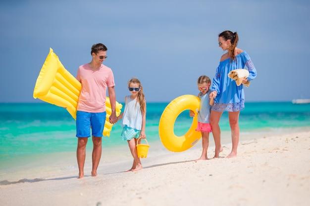 Glückliche schöne familie am weißen strand mit luftmatratzen