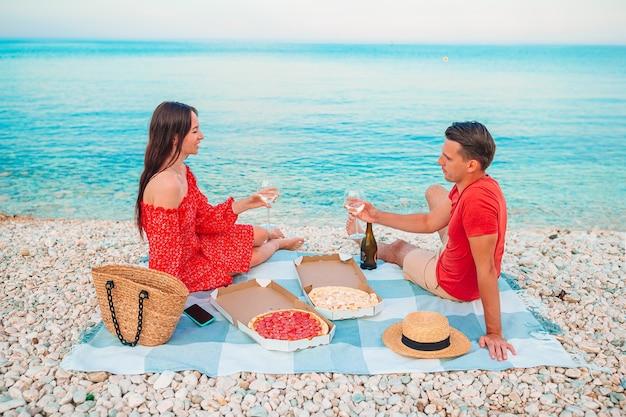Glückliche schöne familie an einem tropischen strand mit picknick zusammen auf dem sonnenuntergang