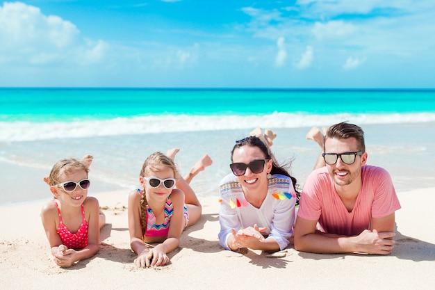 Glückliche schöne familie auf dem weißen strand, der spaß hat