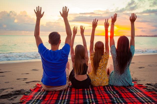 Glückliche schöne familie bei sonnenuntergang am strand