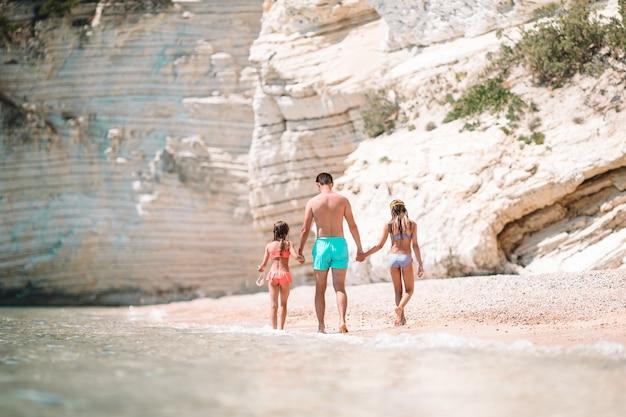 Glückliche schöne familie des vatis und der kinder auf weißem strand