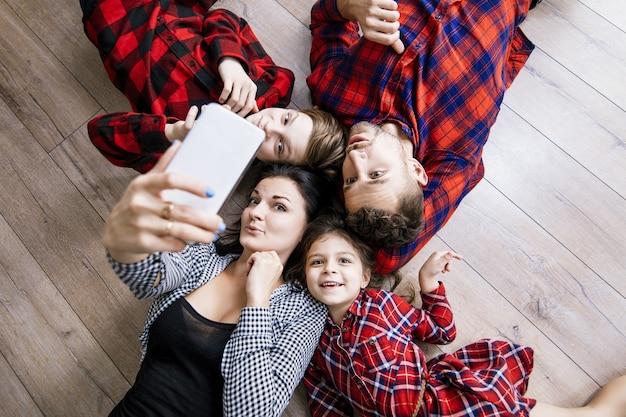 Glückliche schöne familie glücklich, selfie auf handy zusammen zu hause liegend boden zu machen