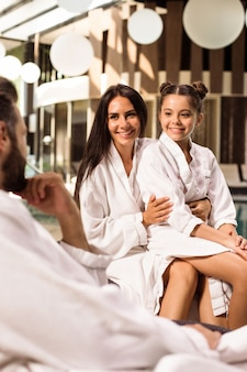 Glückliche schöne familie in bademänteln sind zusammen fröhlich, während sie im spa-salon sitzen