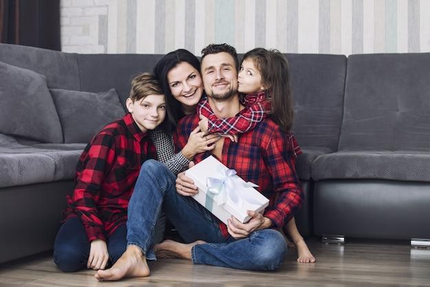 Glückliche schöne familie schenkt dem vater zu diesem anlass gemeinsam zu hause im wohnzimmer ein geschenk