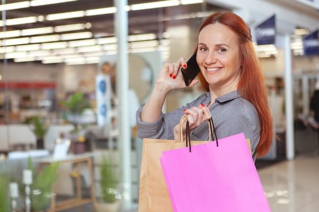 Glückliche schöne frau, die am telefon beim einkaufen im einkaufszentrum spricht, kopieren raum. konsumismus, verkaufskonzept