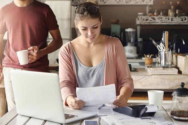 Glückliche schöne frau, die benachrichtigung von bank über verlängerung der hypothekenlaufzeit liest