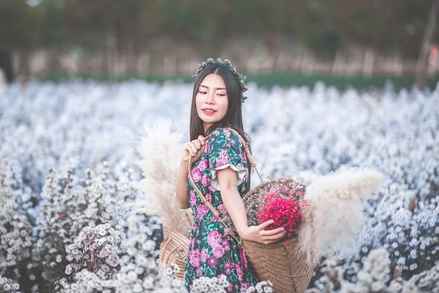 Glückliche schöne frau, die blumenkorb im blumengarten hält