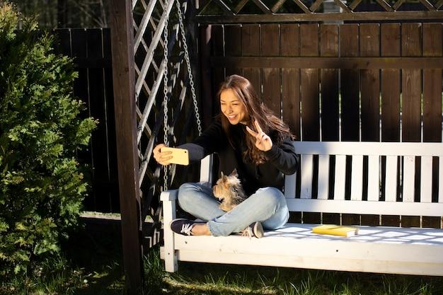 Glückliche schöne frau, die friedenszeichen tut, das auf hölzerner schaukel mit kleinem hundehaustier sitzt und selfie macht