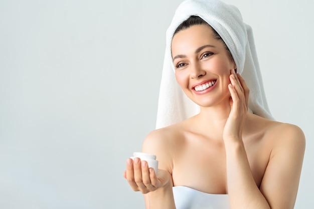Glückliche schöne frau, die ihre wangen mit einem lachen hält, das zur seite schaut. kosmetologie, schönheit und spa