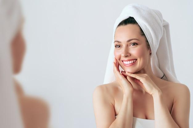 Glückliche schöne frau, die ihre wangen mit einem lachen hält, das zur seite schaut. kosmetologie, schönheit.