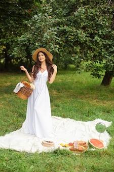 Glückliche schöne frau, die krempenhut und weißes kleid beim stehen und halten des brotkorbs im sommerpark trägt