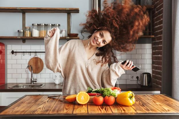 Glückliche schöne frau, die musik auf dem handy hört, während sie frischen gemüsesalat im kücheninnenraum zu hause kocht