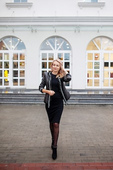 Glückliche schöne frau, die spaß auf stadtstraße hat. modefrau geht auf straße auf hohen absätzen.