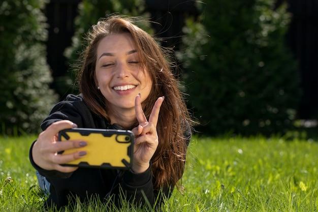 Glückliche schöne frau, die spaß draußen hat, selfie-foto auf handy mit friedenszeichen machend, während auf grünem gras im park liegend