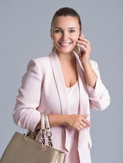 Glückliche schöne frau hält handtasche und handy über weiß