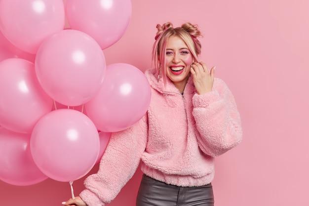 Glückliche schöne frau hat zwei in pelzmantel gekleidete brötchen lächelt gerne trägt make-up hält haufen aufgeblasener luftballons genießt partys und feiern