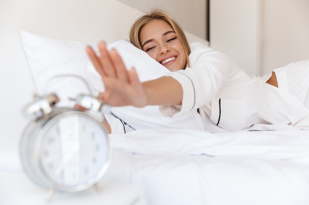 Glückliche schöne frau im pyjama, die den alarm ausschaltet, während sie nach dem schlafen oder nickerchen auf dem bett liegt